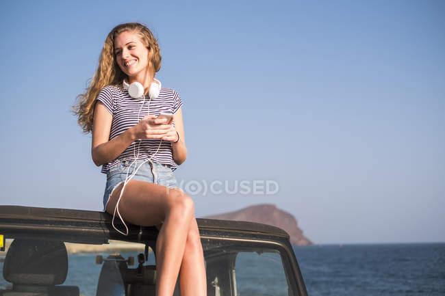 Молодая женщина сидит на машине на пляже со смартфоном и наушниками — стоковое фото