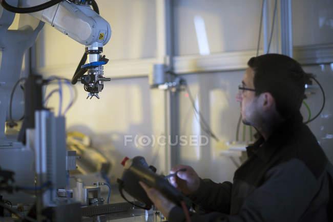 Homem olhando para o braço do robô em uma planta de tecnologia de sensor — Fotografia de Stock