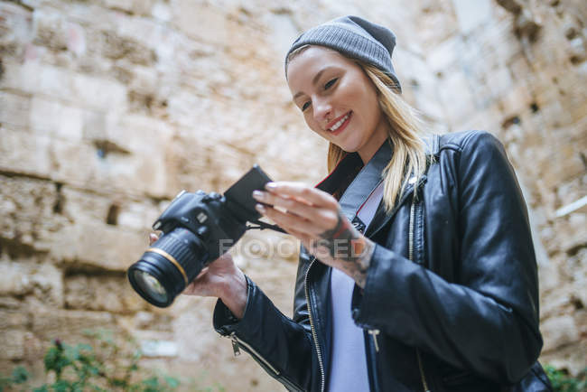 Young woman looking at photos on her camera. — Stock Photo