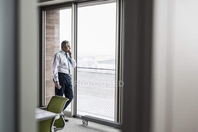 Gerente de pé na janela — Fotografia de Stock