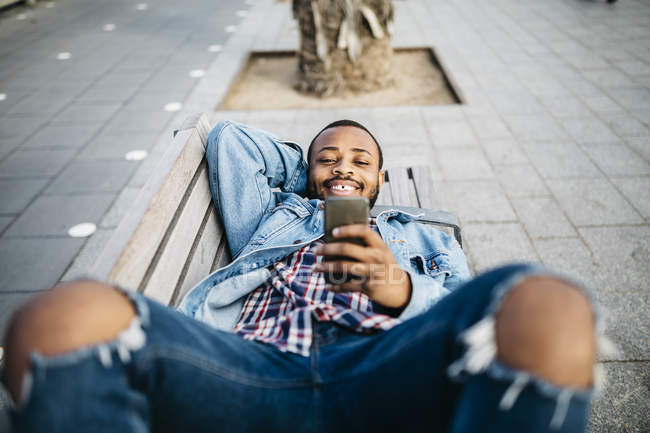 Young traveler lying on banch using mobile, enjoying the city. — Stock Photo