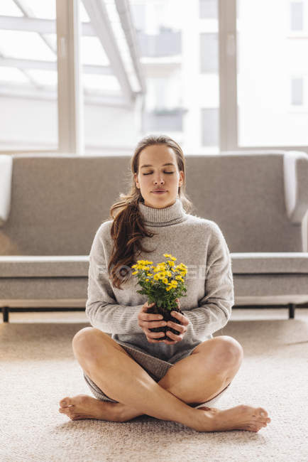 Woman with closed eyes sitting on floor and holding potted flower — Stock Photo