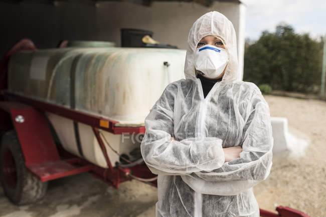 Woman wearing protective overall to fumigate olive trees — Stock Photo