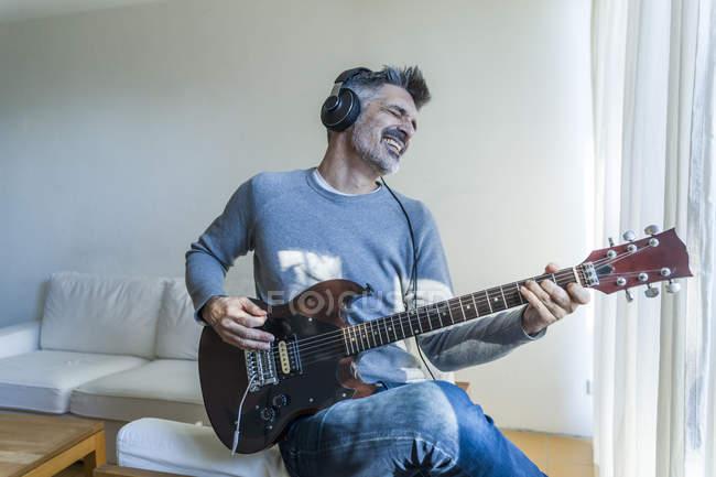 Портрет зрелого человека играть на гитаре — стоковое фото