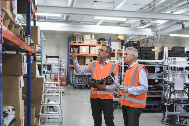 Colleagues standing in factory hall — Stock Photo