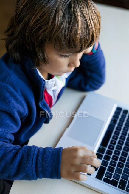 Cropped portrait of boy using laptop at desk — Stock Photo