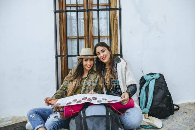 Молода жінка мандрівників сидить з картою — стокове фото