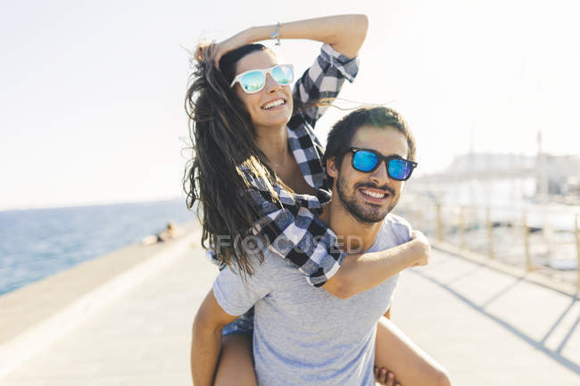 Porträt eines jungen Paares huckepack am Hafen — Stockfoto