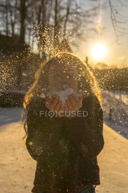 Young woman blowing snow at backlight — Stock Photo