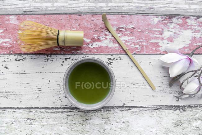 Matchatee, щітка, дерев'яною ложкою на дерев'яні поверхні — стокове фото