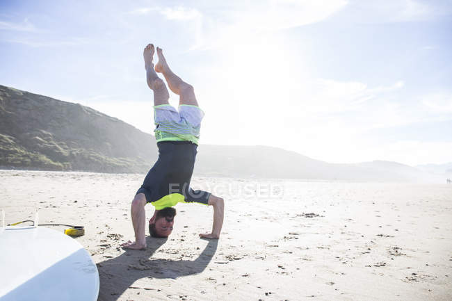 Young man standing on hands upside down on sandy beach in sunny weather — Stock Photo