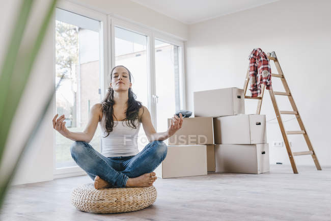 Woman sitting on cushion in new home and meditating — Stock Photo