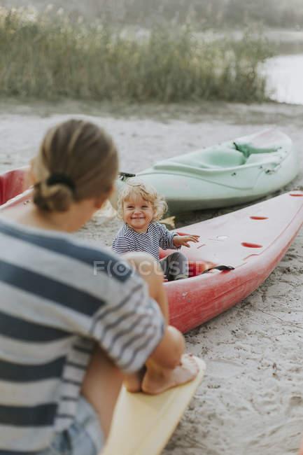 Madre con la piccola figlia seduto in una barca sulla riva — Foto stock