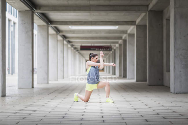 Woman warming up before jogging outdoors — Stock Photo