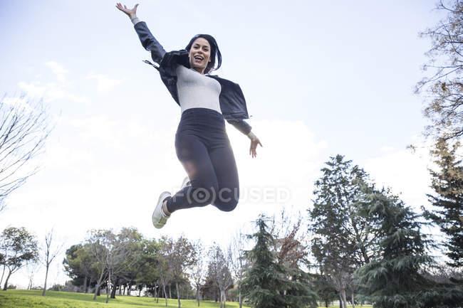 Retrato de uma jovem sorridente pulando no ar — Fotografia de Stock