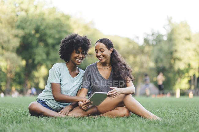 Two best friends sitting on a meadow of a park and sharing mini tablet — Stock Photo