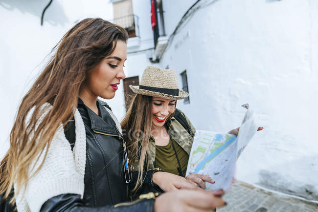 Two traveling women looking at a map in old city — Stock Photo