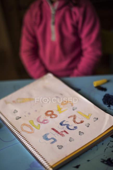 Petite fille à la maison, numéros de dessin dans la vue ordinateur portable — Photo de stock