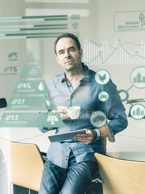 Portrait of mature businessman near digital screen — Stock Photo