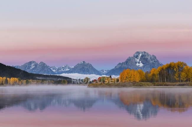 Stati Uniti, Wyoming, montagne rocciose, Teton Range, Parco nazionale Grand Teton e serpente fiume al tramonto — Foto stock