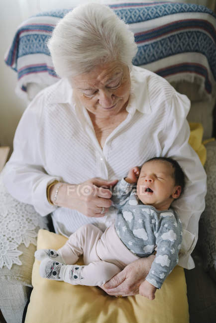 Great-grandmother holding great-granddaughter in armchair at home — Stock Photo