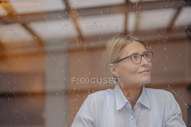 Businesswoman looking away behind windowpane — Stock Photo