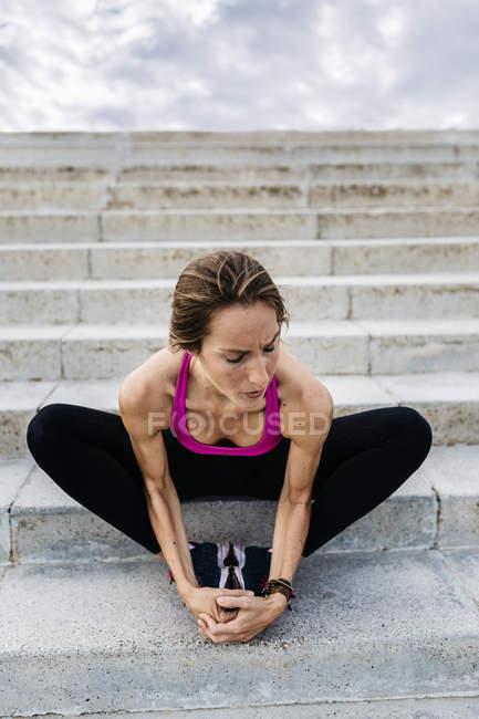 Jeune femme assise sur l'escalier après formation et étirement des jambes — Photo de stock