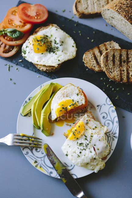 Вид зверху яєчня з скибочками авокадо, тости і помідорами — стокове фото