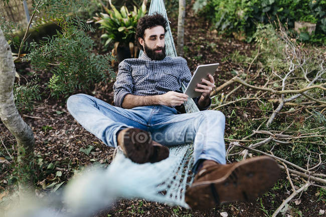 Man on hammock with tablet and  beer. — Stock Photo
