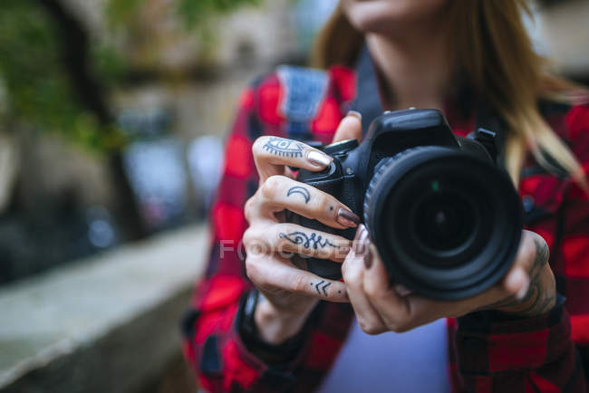 Closeup of tattooed female hands holding a reflex camera — Stock Photo