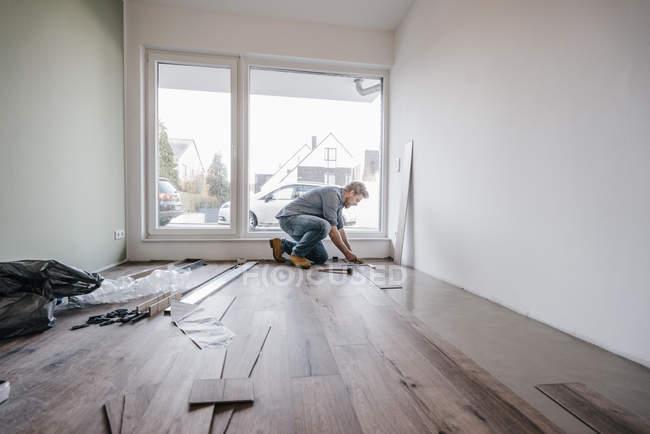 Зріла людина припасування підлоги в новому будинку — стокове фото