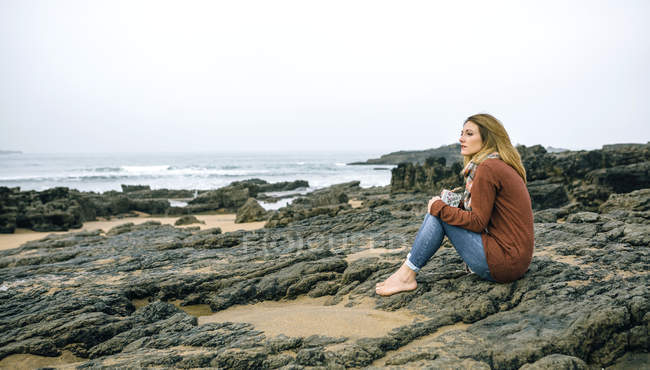 Lonely woman sitting on rocks on the beach in winter — Stock Photo