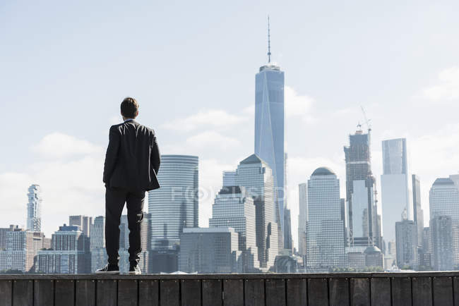 Businessman standing at New Jersey waterfront with view to Manhattan, USA — Stock Photo