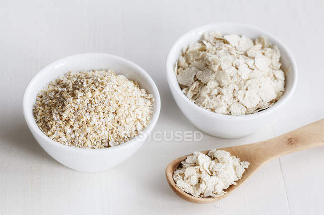 Closeup view of brans and oats in white bowls with wooden spoon — Stock Photo