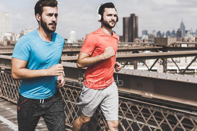 США, Нью-Йорк, Бруклінський міст, двоє молодих людей, біг підтюпцем, міський пейзаж подання на тлі — стокове фото