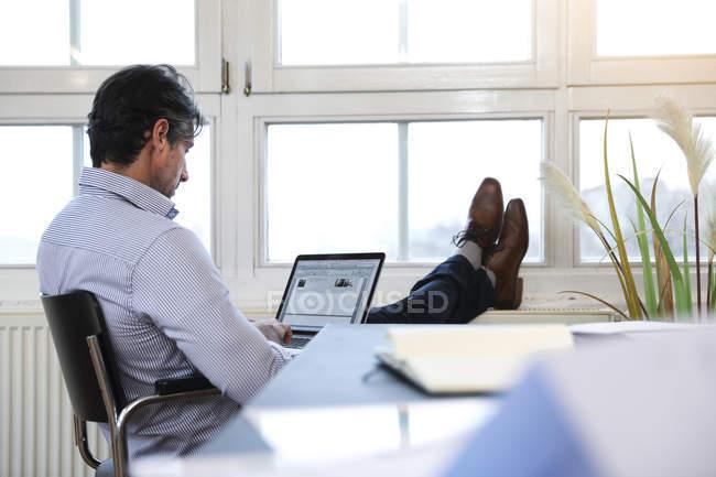 Людина, використовуючи ноутбук у вікно в офісі — стокове фото