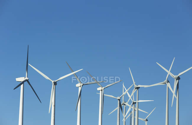 White wind turbines and blue sky on background — Stock Photo