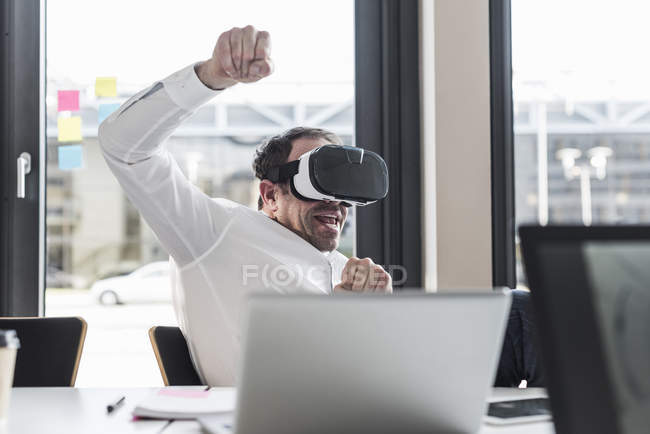 Portrait of businessman wearing virtual reality glasses in office — Stock Photo