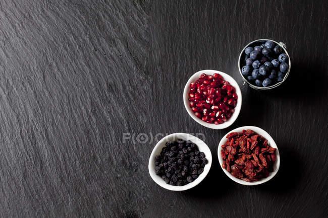 Draufsicht der Heidelbeeren mit Granatapfelkernen, Wolfberries und Chokeberries in Schalen — Stockfoto