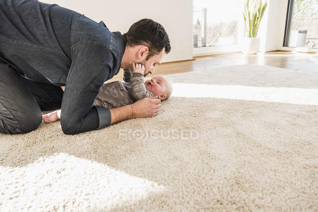 Father and baby son playing on carpet at home — Stock Photo