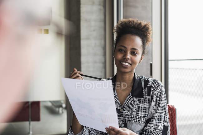 Frau hält Dokument und im Gespräch mit Kollegen — Stockfoto