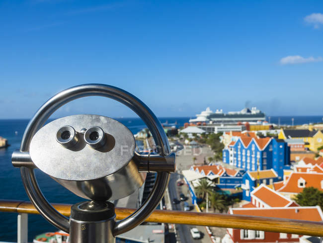 Curacao, Willemstad, Punda, coin-operated binocular and colorful houses at waterfront promenade — Stock Photo