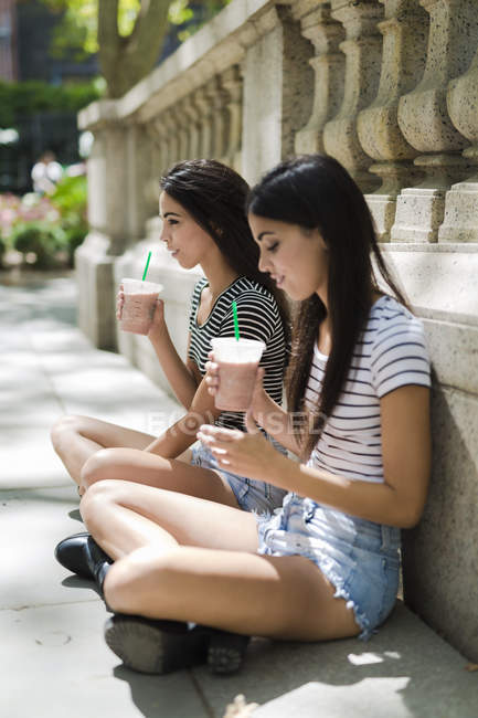 Portrait of two young women with drinks near stone fence — Stock Photo