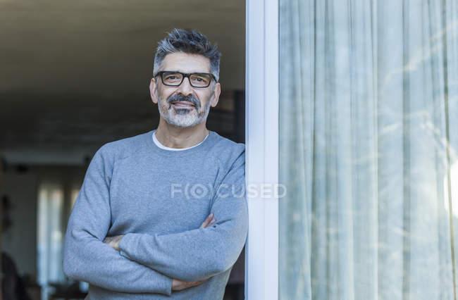 Retrato de homem maduro em pé perto de vidro painel — Fotografia de Stock
