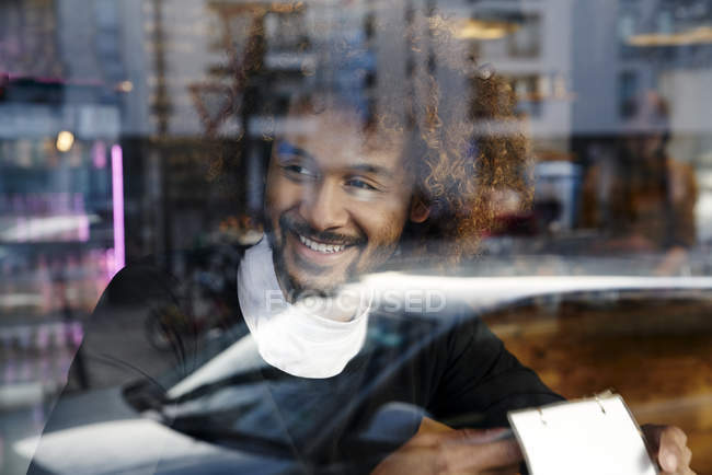 Portrait of smiling young man behind windowpane — Stock Photo