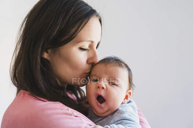 Woman holding and kissing a baby yawning — Stock Photo