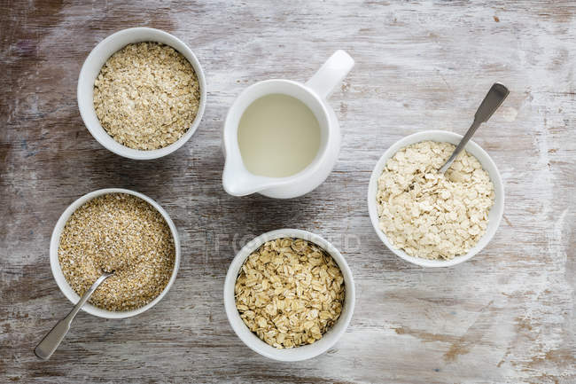 Top view of different sorts of oat flakes in bowls and milk — Stock Photo