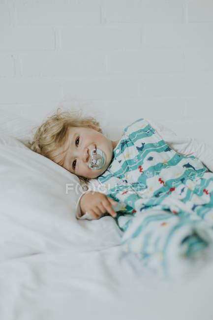 Дівчинка з соску, лежачи на ліжку — стокове фото