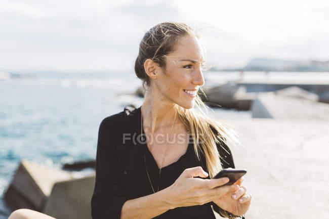 Sorrindo jovem mulher com telefone celular em frente ao mar olhando ao redor — Fotografia de Stock