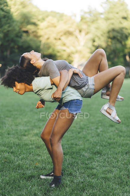 Young woman carrying best friend piggyback in a park — Stock Photo